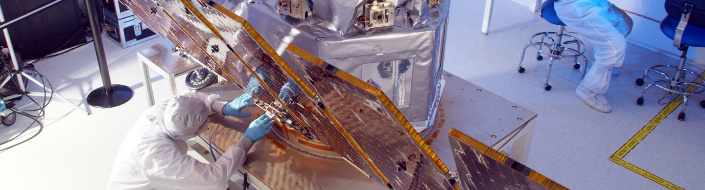 High angle of engineers working on a satellite in a clearnoom