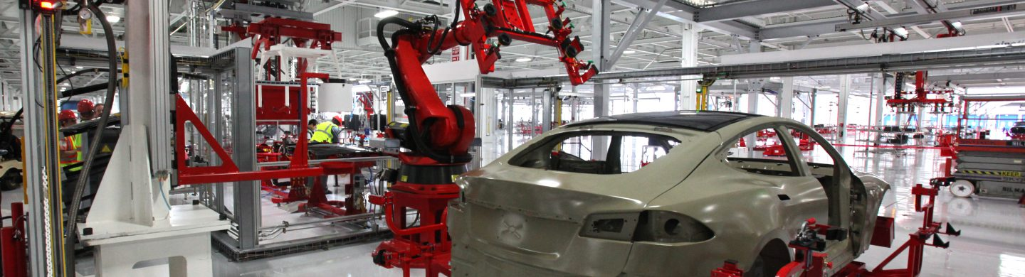 Car factory interior with unpainted car on assembly line