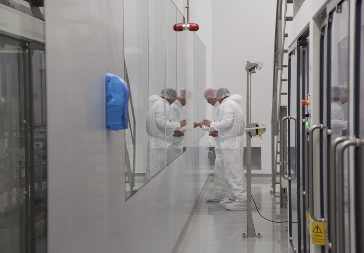 Engineers examining window panels in factory