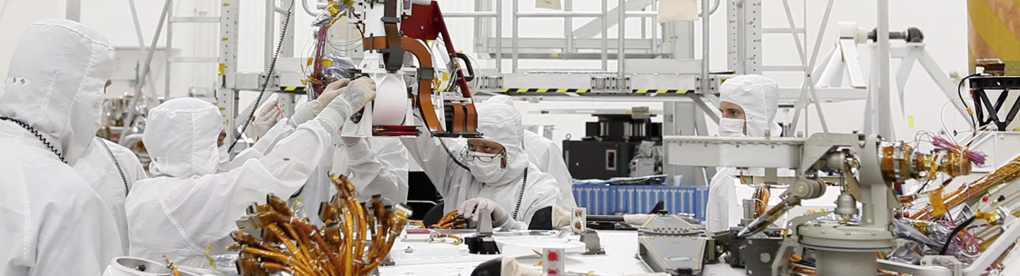 Technicians work on machinery in cleanroom