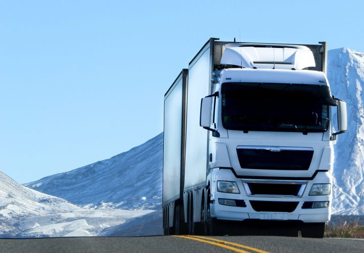 White lorry driving through snowy mountain road