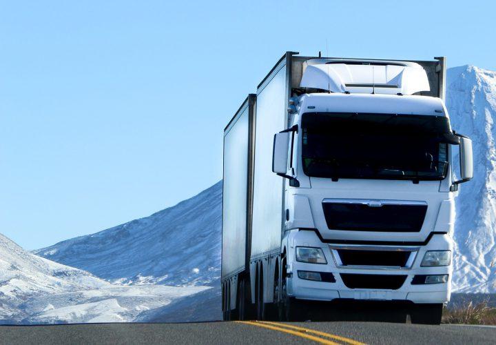 White lorry driving through snowy mountain road