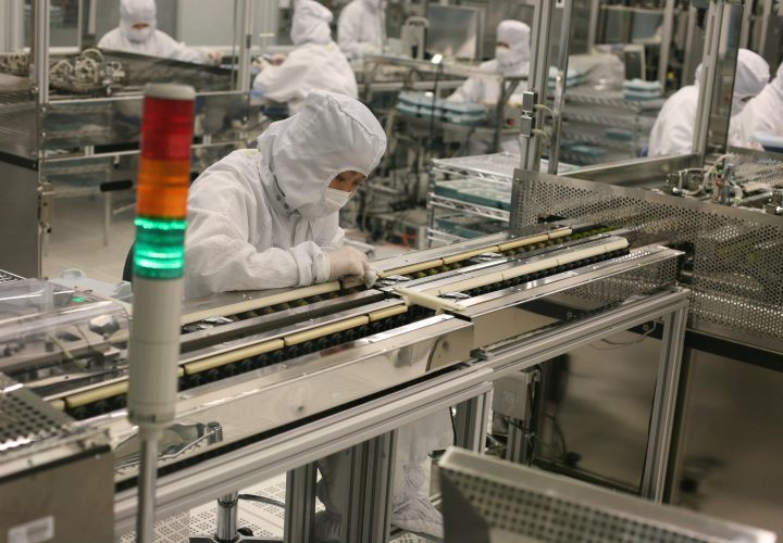 Worker on production line of technology factory